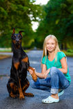 Blonde girl holding dog or doberman paw in summer Royalty Free Stock Photos