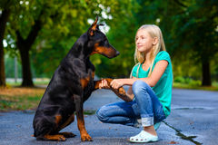 Blonde girl holding dog or doberman paw in summer Royalty Free Stock Images