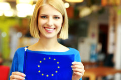 Blonde girl holding flag of europe union. Happy blonde girl holding flag of europe union Royalty Free Stock Photos