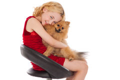 Blonde girl holding  her dog wearing red dress Stock Image