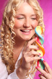 Blonde girl holding lollipop. Over pink royalty free stock images