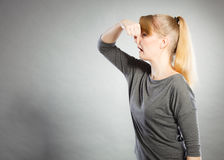 Blonde girl holding nose. Stock Photos