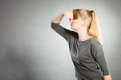 Blonde girl holding nose. Royalty Free Stock Photography