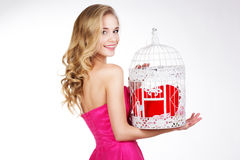 Blonde girl holding white cage with red heart Royalty Free Stock Image