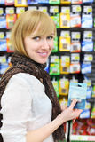 Blonde girl holds battery in shop Stock Image