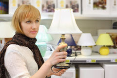 Blonde girl holds beautiful table lamp in shop. Blonde girl wearing scarf holds beautiful table lamp in shop; shallow depth of field stock photo