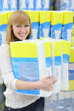 Blonde girl holds big pack of toilet paper Royalty Free Stock Images