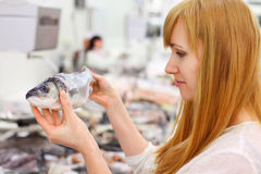 Blonde girl holds fish in store. Blonde girl wearing white shirt holds fish in store; shallow depth of field royalty free stock images