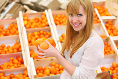 Blonde girl holds oranges in store Royalty Free Stock Images
