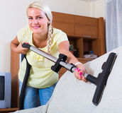 Blonde girl hoovering in living room Royalty Free Stock Images