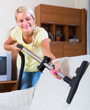 Blonde girl hoovering in living room Royalty Free Stock Photos