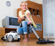 Blonde girl hoovering in living room Royalty Free Stock Photo