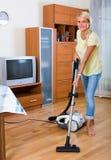 Blonde girl hoovering in living room Royalty Free Stock Image