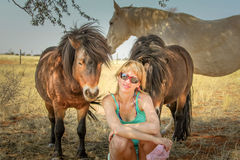 Blonde girl and the horses of the desert Royalty Free Stock Images