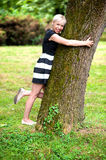 Blonde girl hugging  the tree Royalty Free Stock Photography