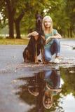 Blonde girl hugs her beloved dog or doberman in Stock Photo