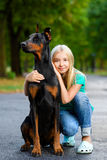 Blonde girl hugs her beloved dog or doberman in Royalty Free Stock Image