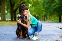 Blonde girl hugs her beloved dog or doberman in Stock Photography