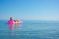 Blonde girl on inflatable raft. Beautiful blonde girl floating on inflatable raft in the sea stock photos