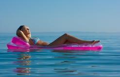 Blonde girl on inflatable raft. Beautiful blonde girl floating on inflatable raft in the sea stock image