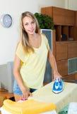 Blonde girl ironing with iron stock photo