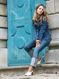 Blonde girl in jeans. Girl in jeans standing before the ancient blue door Stock Photography