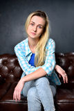 Blonde girl in jeans sits on the leather sofa Stock Photos