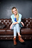 Blonde girl in jeans sits on the leather sofa Royalty Free Stock Photography