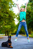 Blonde girl jumping near her beloved dog or Stock Photography