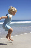 Blonde girl (2-4) jumping on sandy beach at water's edge, profile Stock Photo