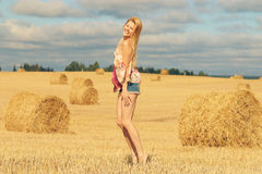 Blonde girl jumps in sloping field Royalty Free Stock Photos