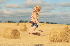 Blonde girl jumps in sloping field Royalty Free Stock Images