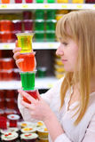 Blonde girl keeps multi-colored jelly in store Royalty Free Stock Image