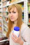 Blonde girl keeps salt in store Stock Photos
