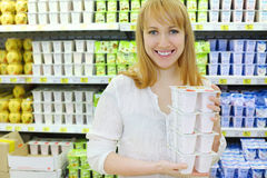 Blonde girl keeps yoghurt in shop. Blonde girl wearing white shirt keeps yoghurt in shop; shallow depth of field stock photos