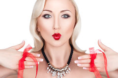 Blonde girl kiss. Beautiful blonde girl showing a kiss and hands with French manicure on which red bows Royalty Free Stock Photo