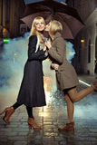 Blonde girl kissing her friend's chick Royalty Free Stock Photos