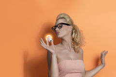 Blonde girl kissing light bulb Royalty Free Stock Images
