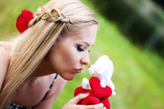 Blonde girl kissing a toy Stock Photography