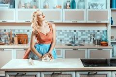 Blonde girl on kitchen kneads dough. royalty free stock photos