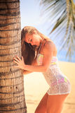 Blonde girl in lace closeup bows head down against long hair. Blonde slim girl in short white lace frock closeup touches palm trunk bows head down against own royalty free stock photography
