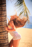 Blonde girl in lace closeup bows head down against long hair. Blonde slim girl in short white lace frock closeup touches palm trunk bows head down against own royalty free stock images