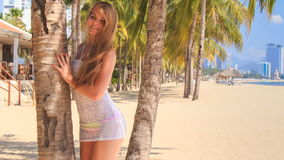 Blonde girl in lace closeup comes to palm trunk on beach stock footage