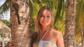 Blonde girl in lace closeup holds palm trunk on beach stock video