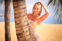 blonde girl in lace closeup leans out of palm smiles on beach Stock Photos
