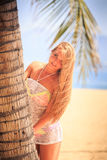 Blonde girl in lace closeup leans out of palm smiles on beach Stock Images