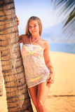 Blonde girl in lace  closeup leans on palm trunk on beach Royalty Free Stock Photos