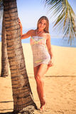 Blonde girl in lace closeup leans on palm trunk on beach Stock Image