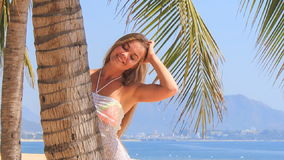 Blonde girl in lace closeup looks out of palm touches hair stock footage