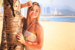 Blonde girl in lace holds palm trunk smiles on beach Stock Image